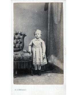 Jeune garçon en robe tenant une raquette. jouet