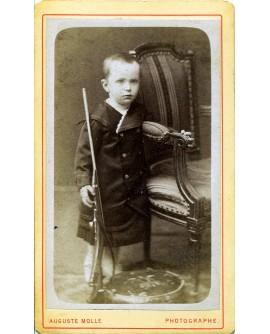 Jeune garçon debout tenant une carabine. jouet