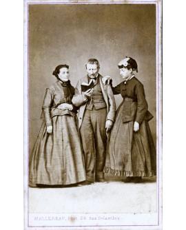 Deux femmes entourant un homme lisant