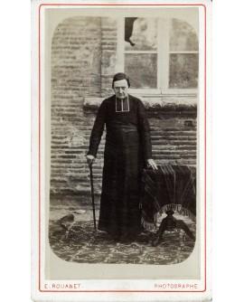 Prêtre debout devant une maison