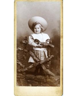 Jeune enfant en robe avec grand chapeau