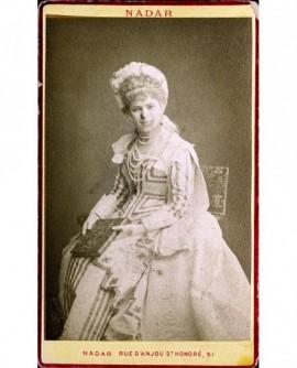 Jeune femme en chapeau assise, un livre à la main