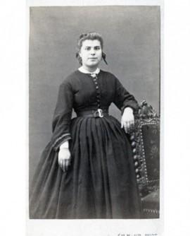 Femme debout appuyée à une chaise