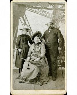 Famille à la Tour Eiffel: femme assise, homme et fillette debout