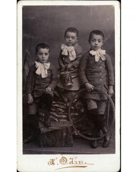 Fratrie de trois (deux garçons et une fille) vêtus pareillement d'une cravate blanche