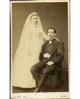 Couple de mariés: homme assis, femme debout la main sur son épaule