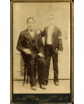 Homme assis, un communiant debout près de lui