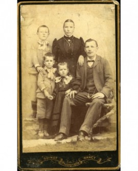 Famille: père assis, mère et les trois enfants debout