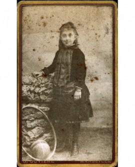 Petite fille debout, cerceau près d'elle (jouet)