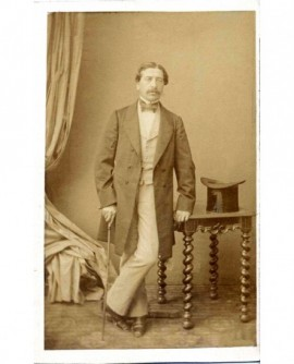 Homme moustachu debout appuyé sur une table et sur une canne