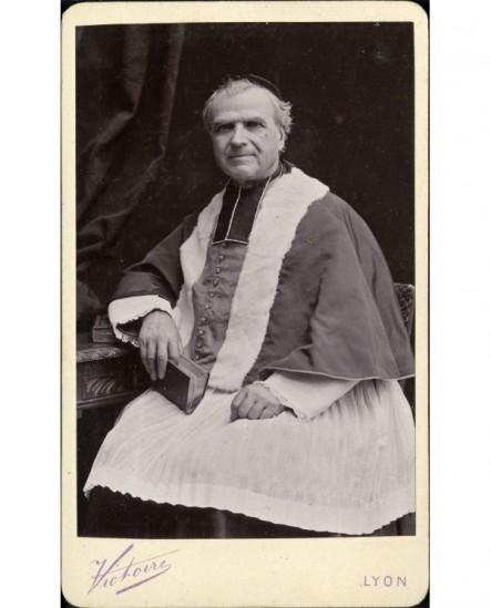 Ecclésiastique en surplis et camail, un livre fermé à la main droite