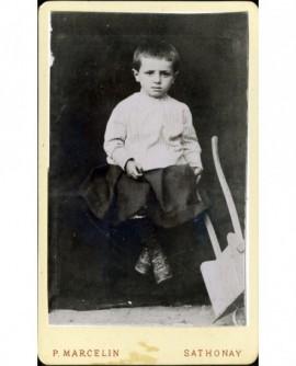 Jeune garçon assis, tenant une petite brouette en bois (jouet)