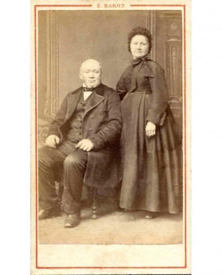 Couple: homme chauve assis, femme en bonnet debout près de lui