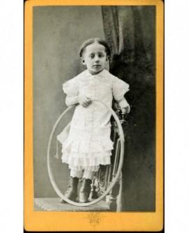 Enfant en robe debout sur une chaise avec cerceau (jouet)