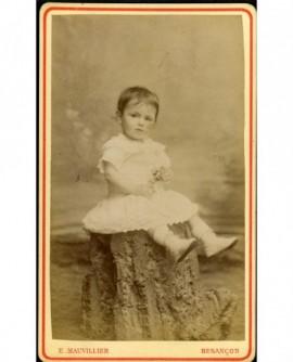 Petite fille en robe assise, une fleur à la main