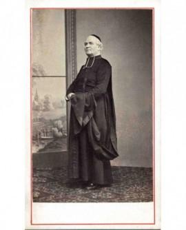 Ecclésiastique debout en calotte, sa douillette sur le bras