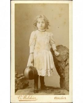 Petite fille en robe blanche debout tenant un ballon