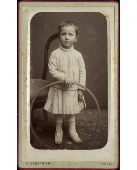 Enfant en robe tenant son cerceau