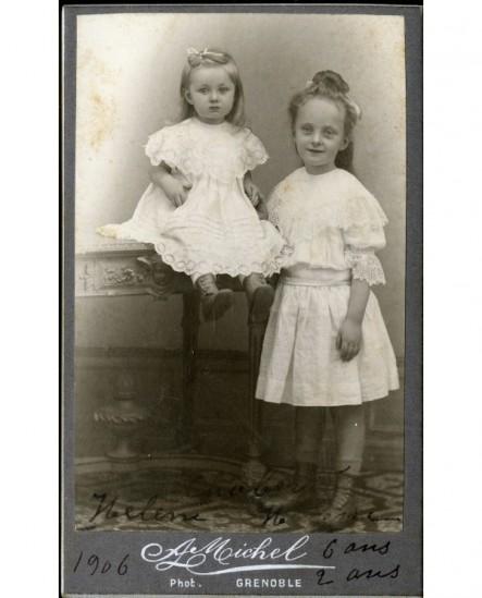 Deux fillettes (soeurs?), la petite assise sur une table