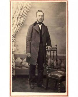 Homme à collier, debout appuyé sur une chaise