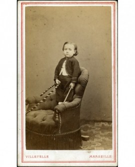 Garçon debout sur un fauteuil avec cerceau. jouet