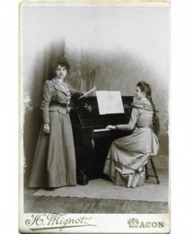 couple de femme, l\'une jouant du piano