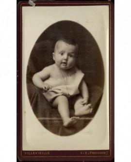 Bébé assis sur un fauteuil, chemise tenue par l'épaule
