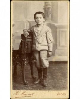Petit garçon accoudé à une chaise