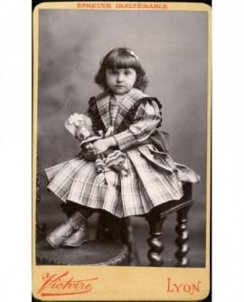 Fillette en robe écossaisse assise, tenant sa poupée