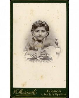 Fillette assise, tenant sa poupée