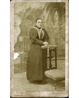 Femme en pied devant la grotte de Lourdes, chapelet à la main