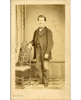 Jeune homme moustachu debout, accoudé à une chaise