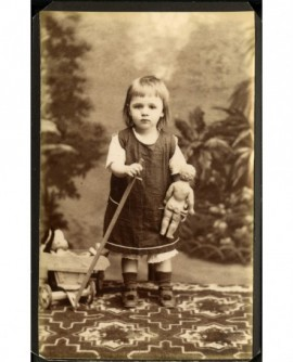 Enfant tirant un chariot, son baigneur à la main