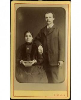 Couple: femme assise tenant un livre, homme moustachu debout