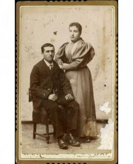 Couple: homme assis et femme debout, appuyée sur lui