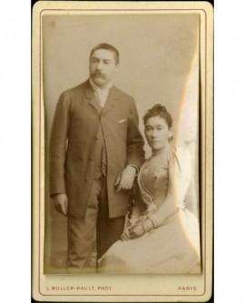 Couple: femme assise, homme moustachu debout