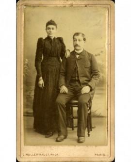 Couple: homme assis, femme debout appuyé sur son épaule