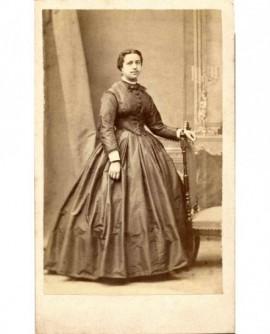 Femme en robe appuyée sur une chaise