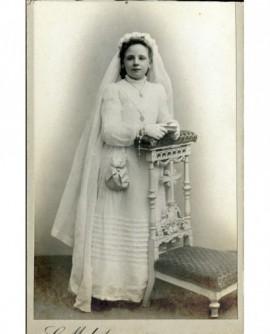 Communiante accoudée à un prie-dieu avec missel et chapelet