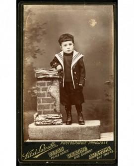 Enfant à col marin, en pied, appuyé sur une stèle factice
