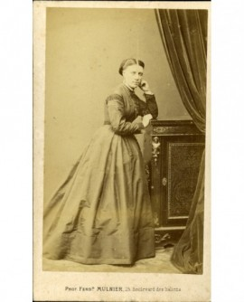 Femme accoudée à un meuble