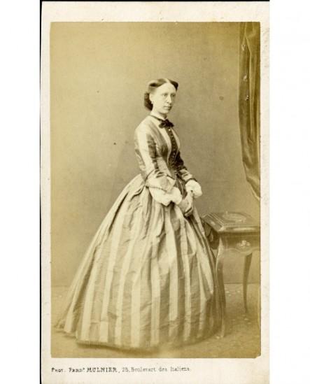 Femme debout, mains jointes, devant une boîte à ouvrage