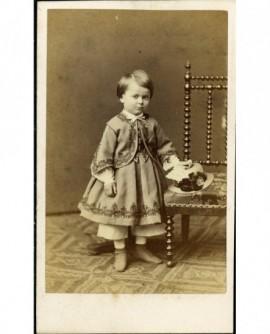 Enfant à costume brodé, son chapeau posé sur une chaise