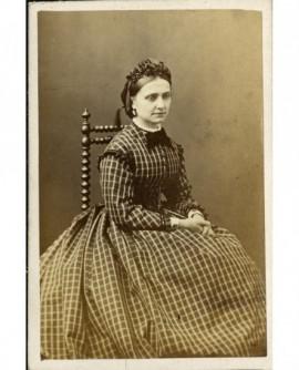 Femme en toque et robe à carreaux assise