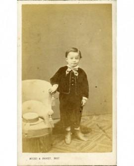 Petit garçon debout, son chapeau posé sur un fauteuil crapaud