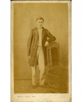 jeune homme debout, accoudé à une chaise