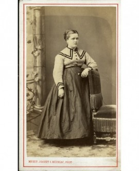 Jeune femme en jupe et corsage debout, appuyée à une chaise