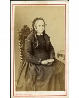 Femme aux macarons en bonnet assise, un livre à la main