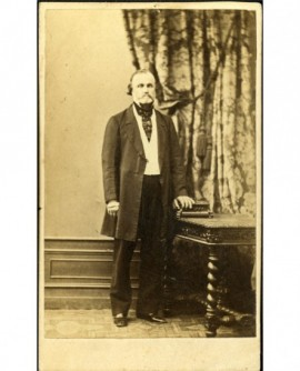 Homme en pied, moustache tombante, main sur une cassette