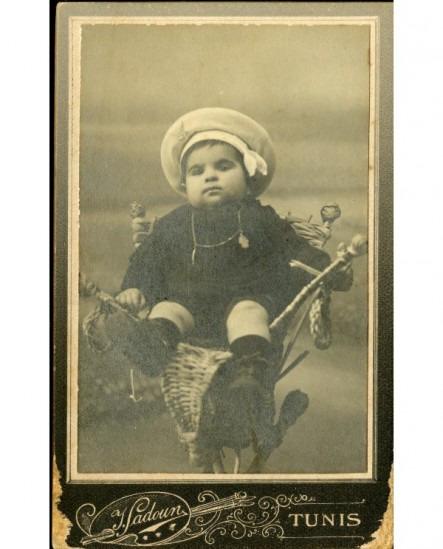 Bébé en béret marin assis dans une corbeille en osier